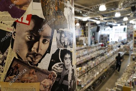 Stock Photo of Portraits of late pop culture icons Tupac Shakur, left, and Lou Reed are plastered on a wall on the re-opening day of the independent record store Amoeba Music Hollywood in a new location on Hollywood Blvd., in Los Angeles. The original store's iconic Sunset Blvd. address closed last April due to the coronavirus pandemic