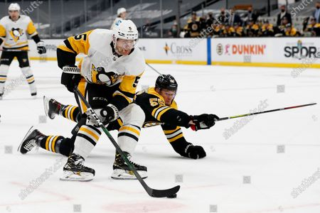Pittsburgh Penguins' Mike Matheson cuts past diving Boston Bruins defenseman Jeremy Lauzon before scoring a goal during the second period of an NHL hockey game, in Boston