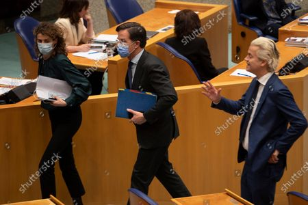 Populist Dutch anti-immigration lawmaker Geert Wilders, right, gestures as caretaker Dutch Prime Minister Mark Rutte, center, leaves during a break ahead of the vote in parliament in The Hague, Netherlands, early Friday morning, . Rutte was fighting for his political life in a bitter parliamentary debate about the country's derailed process of forming a new ruling coalition following elections last month