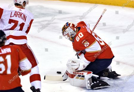Stock Picture of Florida Panthers goaltender Chris Driedger (60) makes a save as Detroit Red Wings center Dylan Larkin (71) closes in during the first period of an NHL hockey game, in Sunrise, Fla