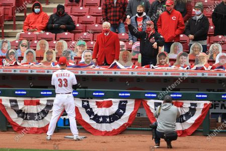 Stock Picture of Cincinnati Reds' right Jesse Winker stands on the field as Sen. Robert Portman, R-Ohio, right, throws out the ceremonial first pitch from the stands prior to a baseball game against the St. Louis Cardinals in Cincinnati, . The Cardinals won 11-6