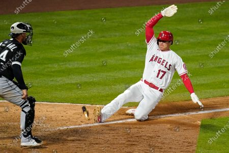 Los Angeles Angels' Shohei Ohtani, right, scores on a ground out by Albert Pujols as Chicago White Sox catcher Yasmani Grandal stands at the plate during the eighth inning of an Opening Day baseball game, in Anaheim, Calif