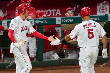 Los Angeles Angels' Shohei Ohtani, left, congratulates Albert Pujols after Ohtani scores on a ground out by Pujols during the eighth inning of an Opening Day baseball game against the Chicago White Sox, in Anaheim, Calif