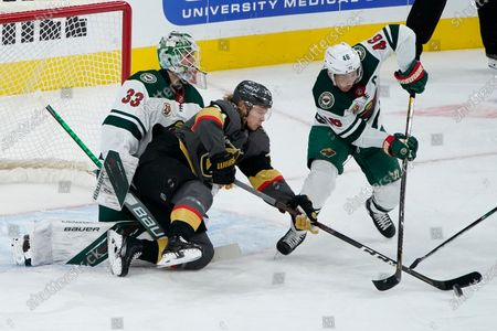 Minnesota Wild defenseman Jared Spurgeon (46) and Vegas Golden Knights center William Karlsson (71) vie for the puck during the first period of an NHL hockey game, in Las Vegas