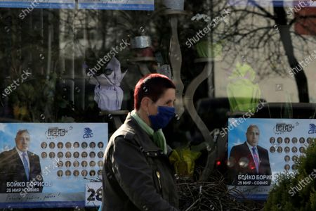 Stock Picture of Woman passes by a poster depicting Bulgarian prime minister Boyko Borissov, in Sofia, Bulgaria, . After months of nationwide anti-government protests over corruption, stalled reforms and a stagnating economy in the EU's poorest member state, Bulgarians are gearing up for a parliamentary election overshadowed by a deadly pandemic
