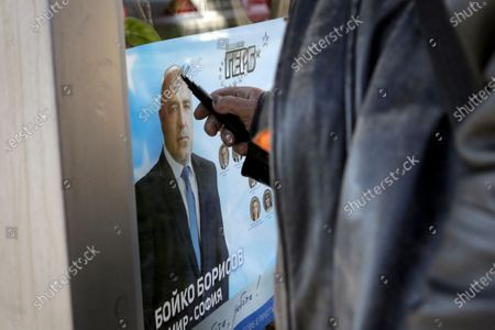 Man draws on poster of Bulgarian prime minister Boyko Borissov in Sofia, Bulgaria, . After months of nationwide anti-government protests over corruption, stalled reforms and a stagnating economy in the EU's poorest member state, Bulgarians are gearing up for a parliamentary election overshadowed by a deadly pandemic