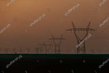 General view of pylons of a high voltage power line at dawn in Villiers le Sec, north of Paris, 02 April 2021.
