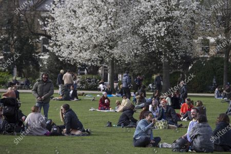 Members of the public enjoy the sun by the canal on Good Friday in Victoria Park, east London.