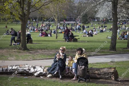 Stock Photo of Members of the public enjoy the sun by the canal on Good Friday in Victoria Park, east London.