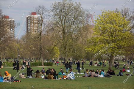 Stock Image of Members of the public enjoy the sun by the canal on Good Friday in Victoria Park, east London.
