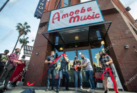 Los Angeles City Councilman Mitch O'Farrell, 2nd from left, holds the ribbon as Karen Pearson and Jim Henderson, co-owners of Amoeba Music on Hollywood Blvd. in Hollywood, successfully cut it during a ceremony in front of the store moments before it reopened in a new location after being shuttered for a year due to the coronavirus outbreak. At right is Rana Ghadban, President and CEO of the Hollywood Chamber of Commerce and at left is Scott Blakeslee with DLJ Real Estate Capital Partners. (Mel Melcon / Los Angeles Times)