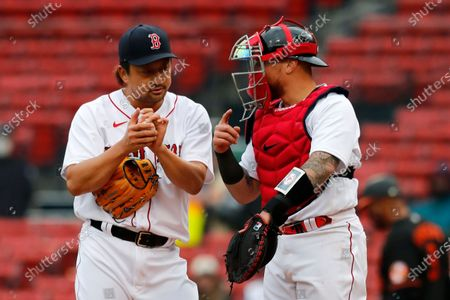 Boston Red Sox's Christian Vazquez, right, talks to Hirokazu Sawamura, center left, on the mound during the ninth inning of an opening day baseball game against the Baltimore Orioles, in Boston