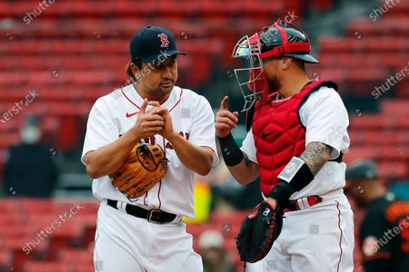 Boston Red Sox's Christian Vazquez, right, talks with Hirokazu Sawamura during the ninth inning of an opening day baseball game against the Baltimore Orioles, in Boston
