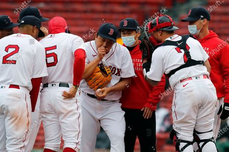 Boston Red Sox's Christian Vazquez (7) talks to Hirokazu Sawamura, center left, on the mound during the ninth inning of an opening day baseball game against the Baltimore Orioles, in Boston