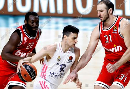Real Madrid's guard Carlos Alocen (C) in action against Olympiakos' guard Charles Jenkins (L) and center Kosta Koufos (R) during the Euroleague game between Real Madrid and Olympiakos B.C. at WiZink Center in Madrid, Spain, 02 April 2021.