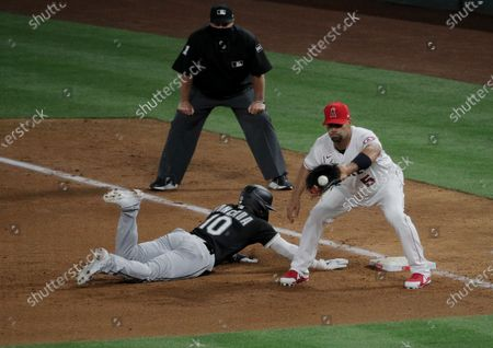 Chicago White Sox third baseman Yoan Moncada (10) gets back to first just in time on a pick off attempt with Los Angeles Angels first baseman Albert Pujols (5) in the sixth inning at Angels Stadium on April 1, 2021 in Anaheim, California.(Gina Ferazzi / Los Angeles Times)