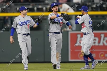 Los Angeles Dodgers left fielder A.J. Pollock, center fielder Cody Bellinger and right fielder Mookie Betts, form left, celebrate the team's 11-6 win over the Colorado Rockies in a baseball game, in Denver