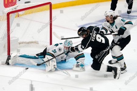 San Jose Sharks goaltender Martin Jones, left, stops a shot by Los Angeles Kings right wing Adrian Kempe, center, as defenseman Erik Karlsson defends during the first period of an NHL hockey game, in Los Angeles