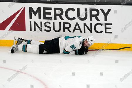 San Jose Sharks defenseman Brent Burns lays on the ice after tripping during the second period of an NHL hockey game against the Los Angeles Kings, in Los Angeles