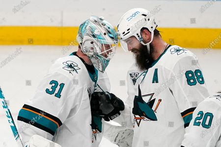 San Jose Sharks goaltender Martin Jones, left, is congratulated by defenseman Brent Burns after the Sharks defeated the Los Angeles Kings 3-0 in an NHL hockey game, in Los Angeles