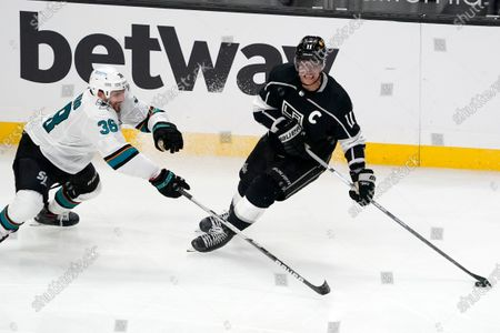 Los Angeles Kings center Anze Kopitar, right, takes the puck as San Jose Sharks defenseman Mario Ferraro reaches for it during the third period of an NHL hockey game, in Los Angeles