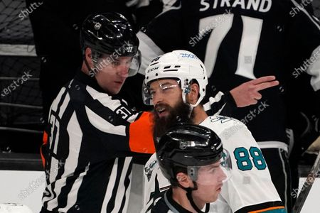 Referee Pierre Lambert, left, gestures as San Jose Sharks defenseman Brent Burns skates by during the third period of an NHL hockey game against the Los Angeles Kings, in Los Angeles