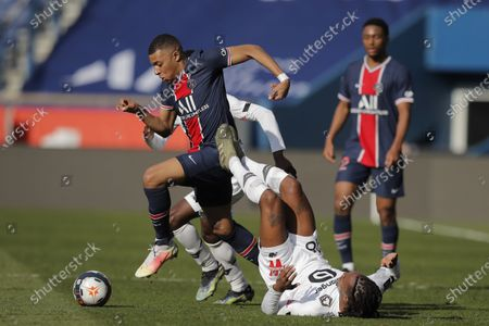 Stock Image of PSG's Kylian Mbappe, left, fights for the ball with Lille's Renato Sanches, on the ground, during the French League One soccer match between Paris Saint Germain and Lille, at the Parc des Princes stadium, in Paris, France