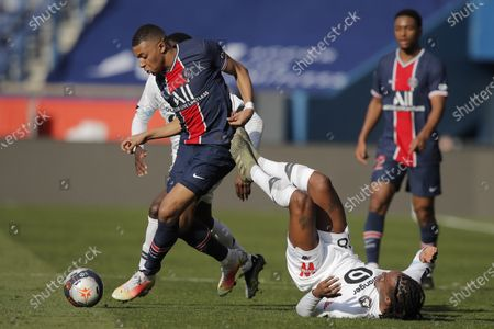 PSG's Kylian Mbappe, left, fights for the ball with Lille's Renato Sanches, on the ground, during the French League One soccer match between Paris Saint Germain and Lille, at the Parc des Princes stadium, in Paris, France