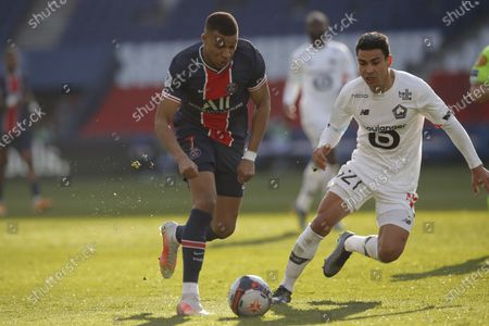 PSG's Kylian Mbappe, left, fights for the ball with Lille's Benjamin Andre during the French League One soccer match between Paris Saint Germain and Lille, at the Parc des Princes stadium, in Paris, France