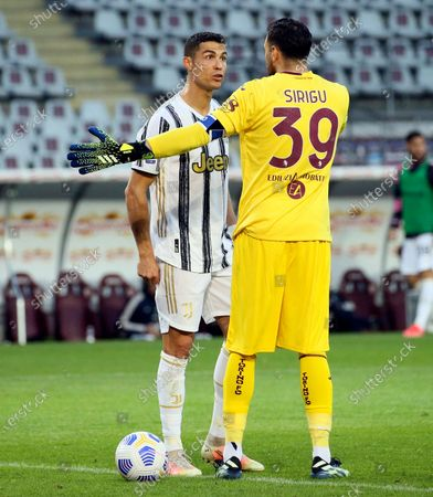 Salvatore Sirigu (L) of Torino FC speak with Cristiano Ronaldo (R) of Juventus during the Serie A match between Torino FC and Juventus at Stadio Olimpico di Torino on April 03, 2021 in Turin, Italy. Sporting stadiums around Italy remain under strict restrictions due to the Coronavirus Pandemic as Government social distancing laws prohibit fans inside venues resulting in games being played behind closed doors.