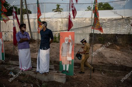 Policeman walks past an image of Indian Prime Minister Narendra Modi as two men wearing masks as a precaution against the coronavirus wait for the arrival of Bharatiya Janata Party (BJP) leader Amit Shah, at an election rally in Alappuzha, Kerala state, India, . The southern state goes to polls on April 6