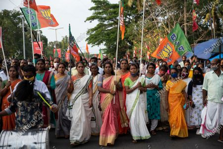 Women carrying Bharatiya Janata Party (BJP) party flags arrive for an election rally addressed by Indian Home Minister Amit Shah, in Alappuzha, Kerala state, India, . The southern state goes to polls on April 6