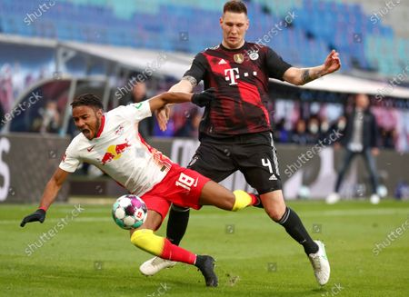 Leipzig's Christopher Nkunku (L) in action against Bayern's Niklas Suele (R) during the German Bundesliga soccer match between RB Leipzig and FC Bayern Munich at Red Bull Arena in Leipzig, Germany, 03 April 2021.