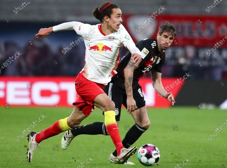 Leipzig's Yussuf Poulsen (L) in action against Bayern's Javi Martinez (R) during the German Bundesliga soccer match between RB Leipzig and FC Bayern Munich at Red Bull Arena in Leipzig, Germany, 03 April 2021.