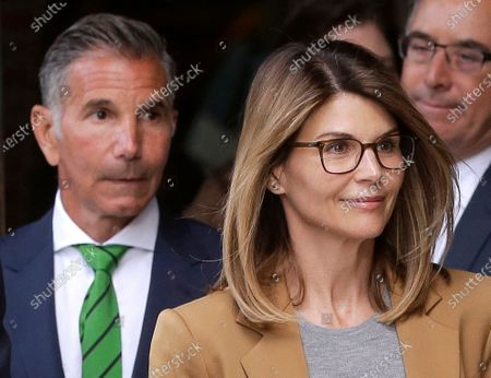 Actress Lori Loughlin, front, and her husband, clothing designer Mossimo Giannulli, left, depart federal court in Boston after facing charges in a nationwide college admissions bribery scandal. Giannulli has been released from a California prison, and is currently at a halfway house outside Los Angeles following his imprisonment for his role in a college admissions bribery scheme, records show