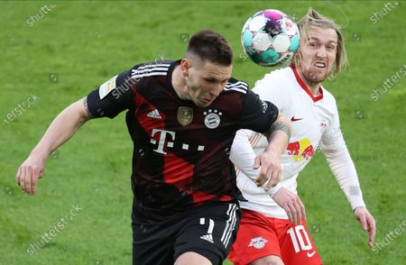 Bayern's Niklas Suele (L) in action against Leipzig's Emil Forsberg (R) during the German Bundesliga soccer match between RB Leipzig and FC Bayern Munich at Red Bull Arena in Leipzig, Germany, 03 April 2021.
