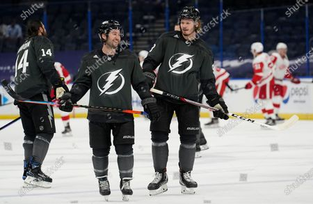 Tampa Bay Lightning center Tyler Johnson talks to defenseman Mikhail Sergachev (98) before an NHL hockey game against the Detroit Red Wings, in Tampa, Fla
