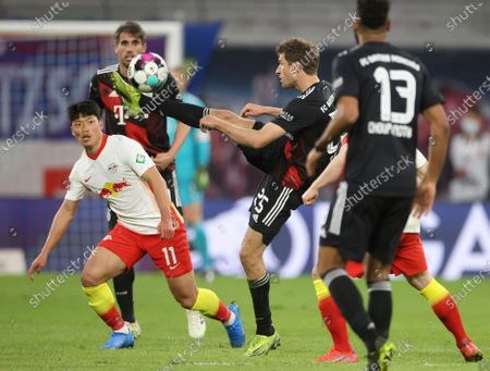Bayern's Thomas Mueller, centre controls the ball as Leipzig's Hwang Hee-chan, left looks on during the German Bundesliga soccer match between RB Leipzig and Bayern Munich, in Leipzig, Germany