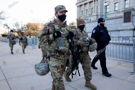 Members of the National Guard and a US Capitol Police Officer (R) patrol outside a perimeter security fence at the US Capitol in Washington, DC, USA, 03 April 2021. Capitol Police Officer William Evans was killed and a second officer was injured when a suspect rammed a vehicle at a security checkpoint at the US Capitol, 02 April. The suspect, identified by law enforcement officials as Noah Green, was shot and killed in the incident. This attack on the Capitol follows the deadly mob riot of 06 Janaury that left dozens injured and five dead.
