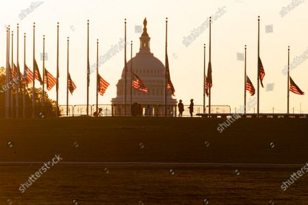 US national flags fly at half staff at the base of the Washington Monument on the National Mall at dawn, with the US Capitol behind, to honor Capitol Police Officer William Evans who was killed as a result of injuries sustained in the 02 April attack on the Capitol, in Washington, DC, USA, 03 April 2021. Capitol Police Officer William Evans was killed and a second officer was injured when a suspect rammed a vehicle at a security checkpoint at the US Capitol, 02 April. The suspect, identified by law enforcement officials as Noah Green, was shot and killed in the incident. This attack on the Capitol follows the deadly mob riot of 06 Janaury that left dozens injured and five dead.