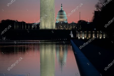 The US Capitol (R) and Washington Monument are seen at dawn behind the Lincoln Memorial Reflecting Pool on the National Mall in Washington, DC, USA, 03 April 2021. Capitol Police Officer William Evans was killed and a second officer was injured when a suspect rammed a vehicle at a security checkpoint at the US Capitol, 02 April. The suspect, identified by law enforcement officials as Noah Green, was shot and killed in the incident. This attack on the Capitol follows the deadly mob riot of 06 Janaury that left dozens injured and five dead.