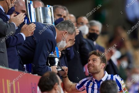 King Felipe VI of Spain gives the Champion Cup to Asier Illarramendi of Real Sociedad after the Copa Del Rey Final match between Real Sociedad and Athletic Club at Estadio de La Cartuja on April 3, 2021 in Seville, Spain. Sporting stadiums around Spain remain under strict restrictions due to the Coronavirus Pandemic as Government social distancing laws prohibit fans inside venues resulting in games being played behind closed doors.