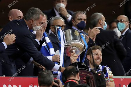Real Sociedad's captain Asier Illarramendi (R) receives the trophy from Spain's King Felipe VI (L) after winning the 2020 Spanish King's Cup final soccer match against Athletic Club  at La Cartuja stadium in Seville, Andalusia, Spain, 03 April 2021.