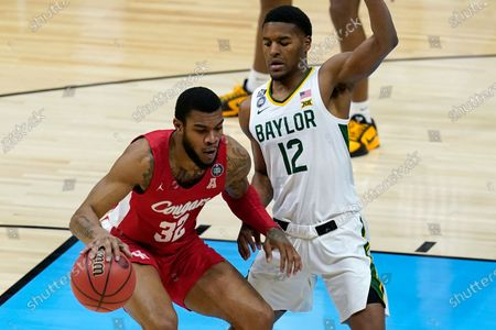 Houston forward Reggie Chaney (32) drives on Baylor guard Jared Butler (12) during the first half of a men's Final Four NCAA college basketball tournament semifinal game, at Lucas Oil Stadium in Indianapolis