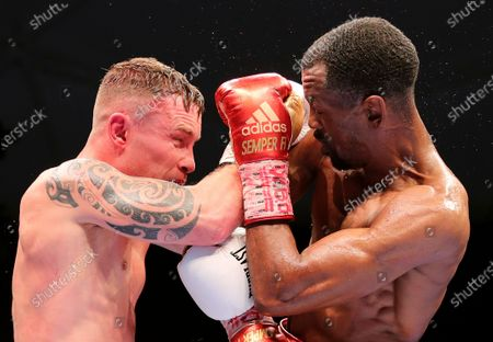 Jamel Herring of the United States, right, and Britain's Carl Frampton exchange blows during their WBO super-featherweight world title fight in Dubai, UAE, early