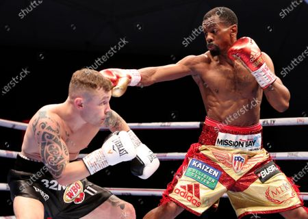 Jamel Herring of the United States, right, lands a blow on Britain's Carl Frampton during their WBO super-featherweight world title fight in Dubai, UAE, early