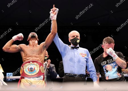 Jamel Herring of the United States, left, has his arm raised in celebration after stopping Britain's Carl Frampton in the sixth round to win their WBO super-featherweight world title fight in Dubai, UAE, early