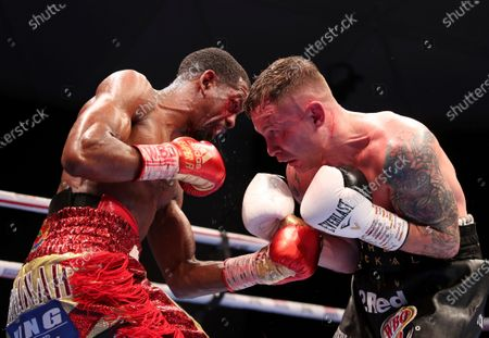 Jamel Herring of the United States, left, and Britain's Carl Frampton exchange blows during their WBO super-featherweight world title fight in Dubai, UAE, early