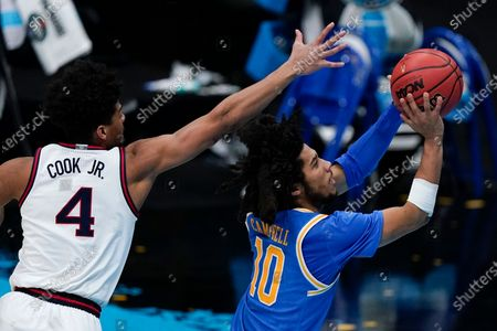 Guard Tyger Campbell (10) shoots ahead of Gonzaga guard Aaron Cook (4) during the second half of a men's Final Four NCAA college basketball tournament semifinal game, at Lucas Oil Stadium in Indianapolis