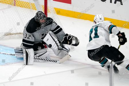 Los Angeles Kings goaltender Jonathan Quick, left, stops a shot by San Jose Sharks defenseman Nikolai Knyzhov during the third period of an NHL hockey game, in Los Angeles